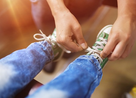 tying: Father tying shoe laces of his son traveling in train. Stock Photo