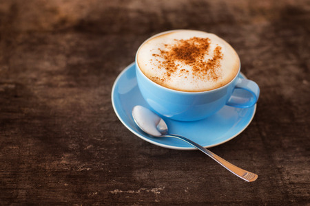blue top: Cup of coffee on a wooden table background