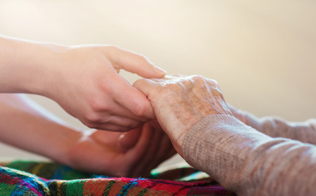 Unrecognizable grandmother and her granddaughter holding hands. photo