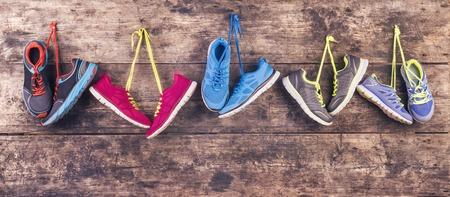 Cinco pares de zapatos para correr varios cuelgan de un clavo en un fondo de cerca de madera Foto de archivo