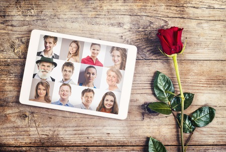 Valentine�s day composition of yet not written love message in a tablet and a red rose. Studio shot on a wooden floor backround. Stock fotó