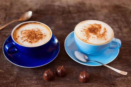 Two cups of coffee on a wooden table background Imagens