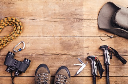 Equipment for hiking on a wooden floor background Archivio Fotografico