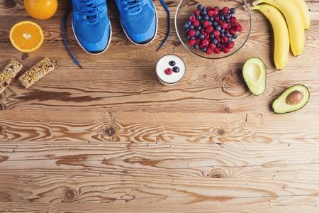 Par de zapatos de correr y de composición de alimentos saludables en un fondo de la tabla de madera Foto de archivo - 38363630