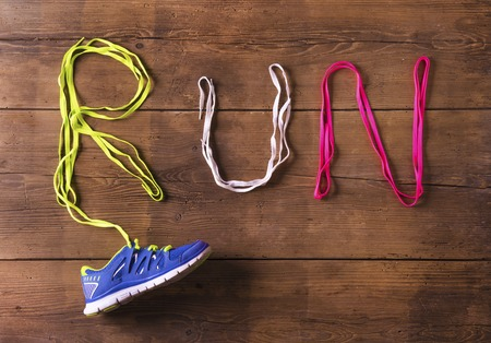 running shoes: Running shoe and shoelaces run sign on a wooden floor background Stock Photo