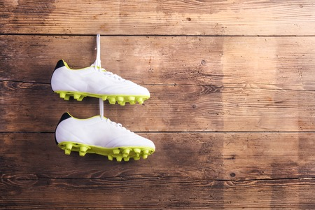 football shoes: Pair of football shoes hang on a nail on a wooden fence background