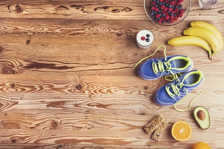 exercises: Pair of running shoes and healthy food composition on a wooden table background