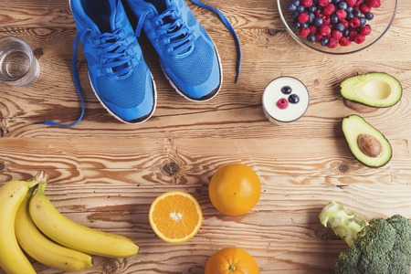 alimentos saludables: Par de zapatos de correr y de composici�n de alimentos saludables en un fondo de la tabla de madera Foto de archivo