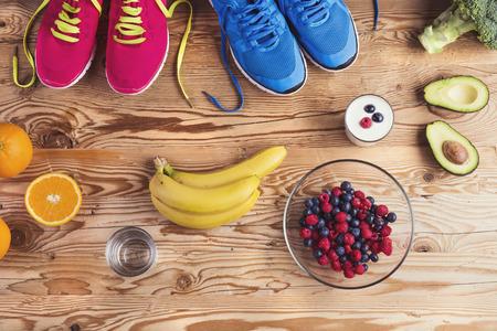 deporte: Zapatos corrientes y composici�n de los alimentos saludables en un fondo de la tabla de madera