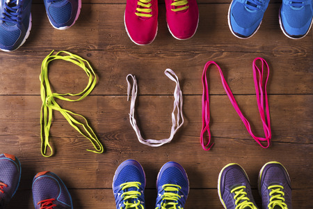Six pairs of running shoes and shoelaces run sign on a wooden floor background