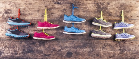 Five pairs of various running shoes hang on a nail on a wooden fence background photo