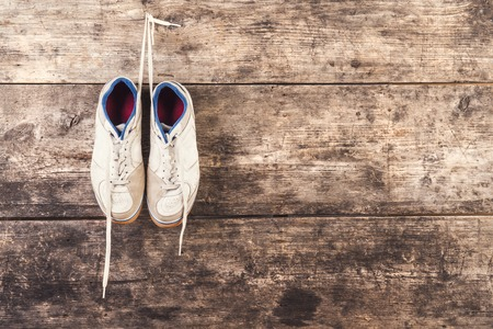 futsal: Pair of sports shoes hang on a nail on a wooden fence background