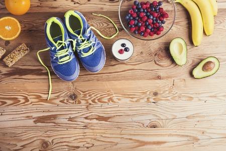 složení: Pár běžeckých bot a zdravé jídlo složení na dřevěný stůl pozadí