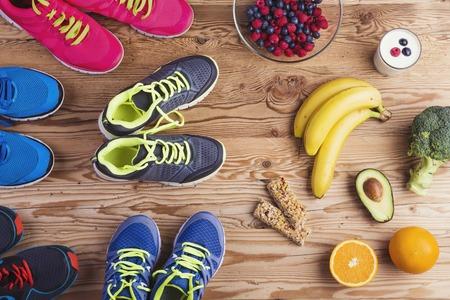 Zapatos corrientes y composición de los alimentos saludables en un fondo de la tabla de madera