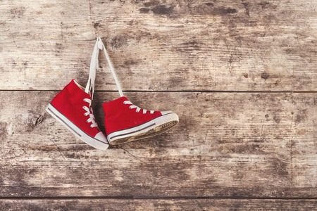 wooden shoes: Pair of red sports shoes hang on a nail on a wooden fence background