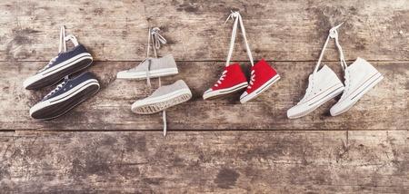 木製フェンスの背景に爪にハングアップするスポーツの靴の 4 つのペア 写真素材