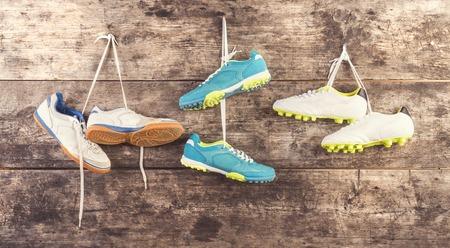 Drie paar sportschoenen hangen aan een spijker op een houten hek achtergrond Stockfoto