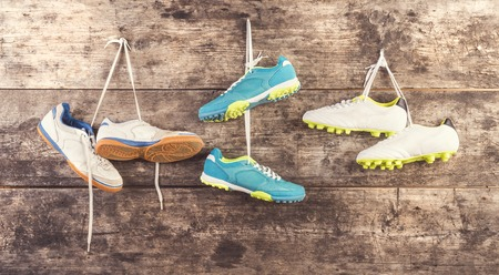 Three pairs of sports shoes hang on a nail on a wooden fence background photo