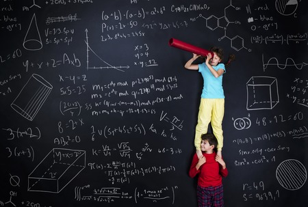 Cute boy and girl learning playfully in frot of a big blackboard. Studio shot on black . Stock Photo