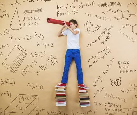 Cute little boy learning playfully in frot of a big blackboard. Studio shot on beige .
