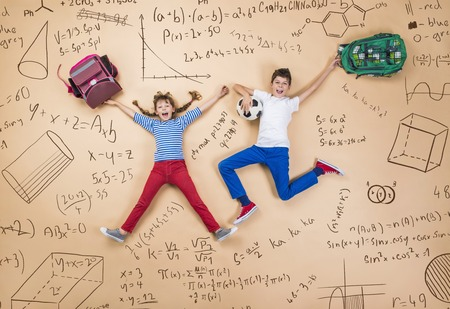 smart girl: Cute boy and girl learning playfully in frot of a big blackboard. Studio shot on beige . Stock Photo