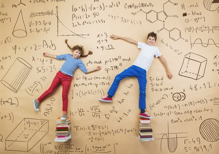 cute young boy: Cute boy and girl learning playfully in frot of a big blackboard. Studio shot on beige background. Stock Photo