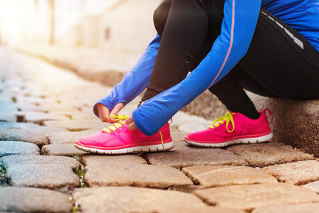 outdoors woman: Unrecognizable young runner tying up her shoelaces Stock Photo