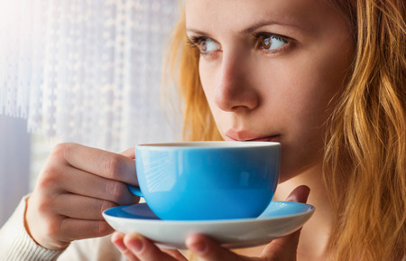 Beautiful woman sipping coffee from her cup photo