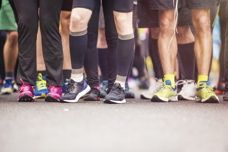 competing: Detail of the legs of runners at the start of a marathon race Stock Photo