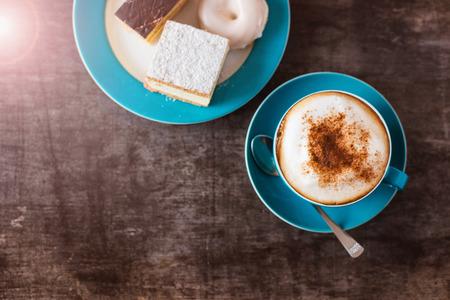 porcion de torta: El café y pasteles en una mesa de madera