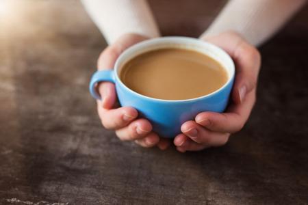나무 테이블에 커피 한 잔을 들고 인식 할 수없는 여자