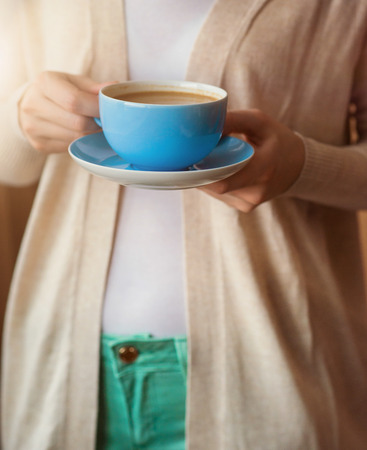 Unrecognizable woman holding a cup of coffee in her hands photo