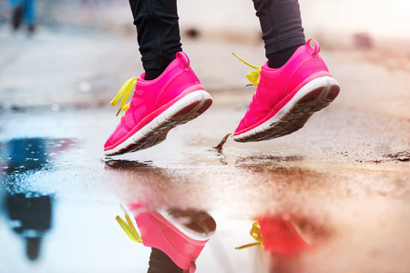 sports race: Unrecognizable young woman running in rainy weather Stock Photo