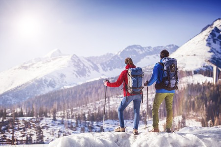 Young couple hiking outside in sunny winter mountains photo