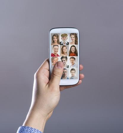 Hand with smart phone. Studio shot on gray . photo