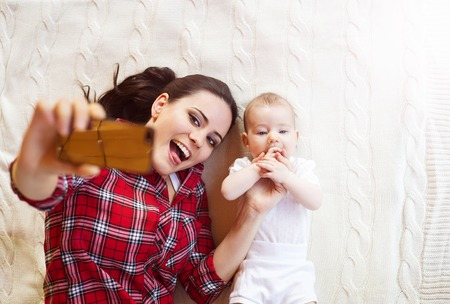 Cute little baby girl and her mother taking selfie on a blanket in a living room. photo