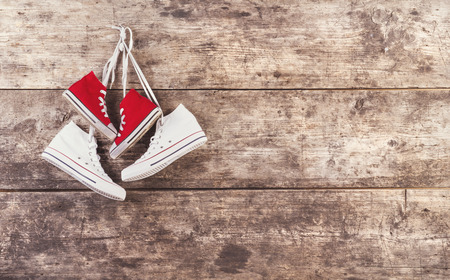 Two pairs of sneakers hang on a nail on a wooden fence background photo