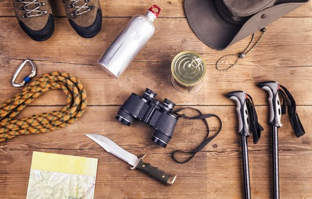 hiking shoes: Equipment for hiking on a wooden floor background Stock Photo