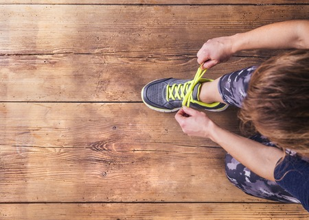 認識できない若いランナーが彼女の靴ひもを結ぶします。スタジオは木の床の背景に撮影。