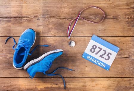 ランニング シューズのペア、木の床の背景にメダルとレース番号