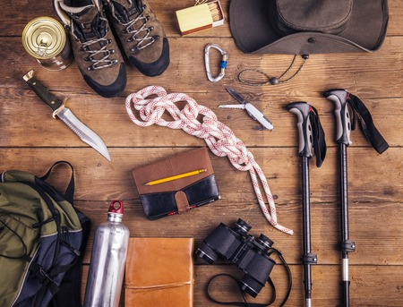 Equipment for hiking on a wooden floor background Foto de archivo
