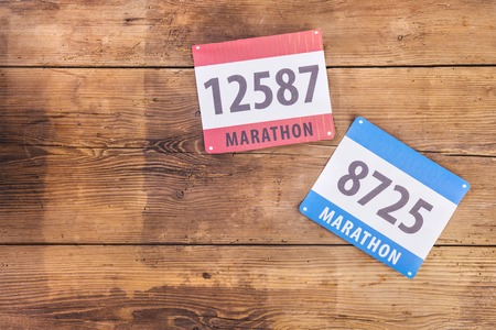 Two marathon race number laid on a wooden floor background