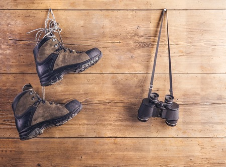 hiking shoes: Hiking shoes and binoculars hang on a wooden fence background