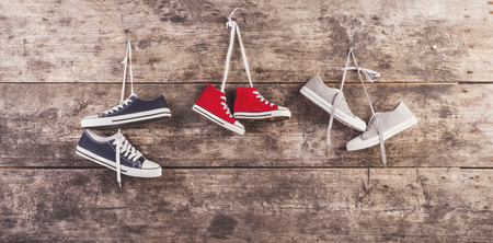 Three pairs of sneakers hang on a nail on a wooden fence background Archivio Fotografico