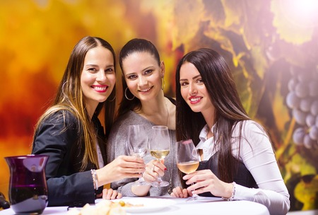 Three beautiful women having fun in a wine bar Stock Photo