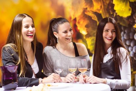 vestido de noche: Tres mujeres hermosas que se divierten en un bar de vinos