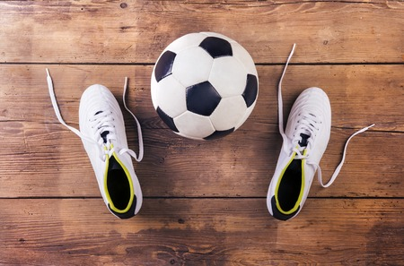 soccer cleats: Football boots and ball laid on a wooden floor background Stock Photo