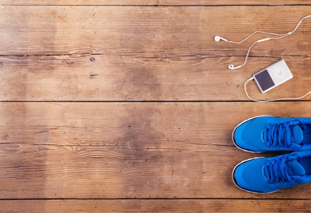 Running shoes and mp3 player on a wooden floor background photo