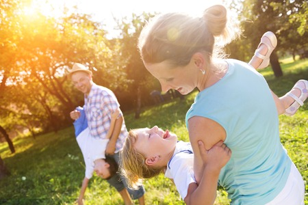 Happy young family spending time together outside in green nature. Stockfoto