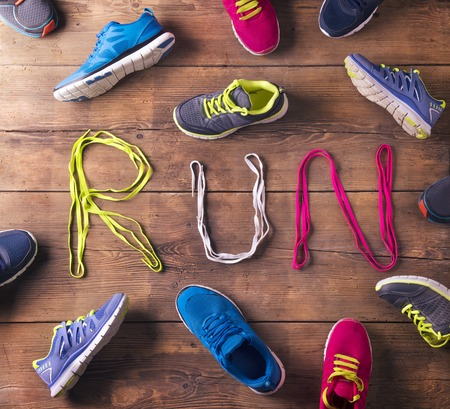 Various running shoes and shoelaces run sign on a wooden floor background photo
